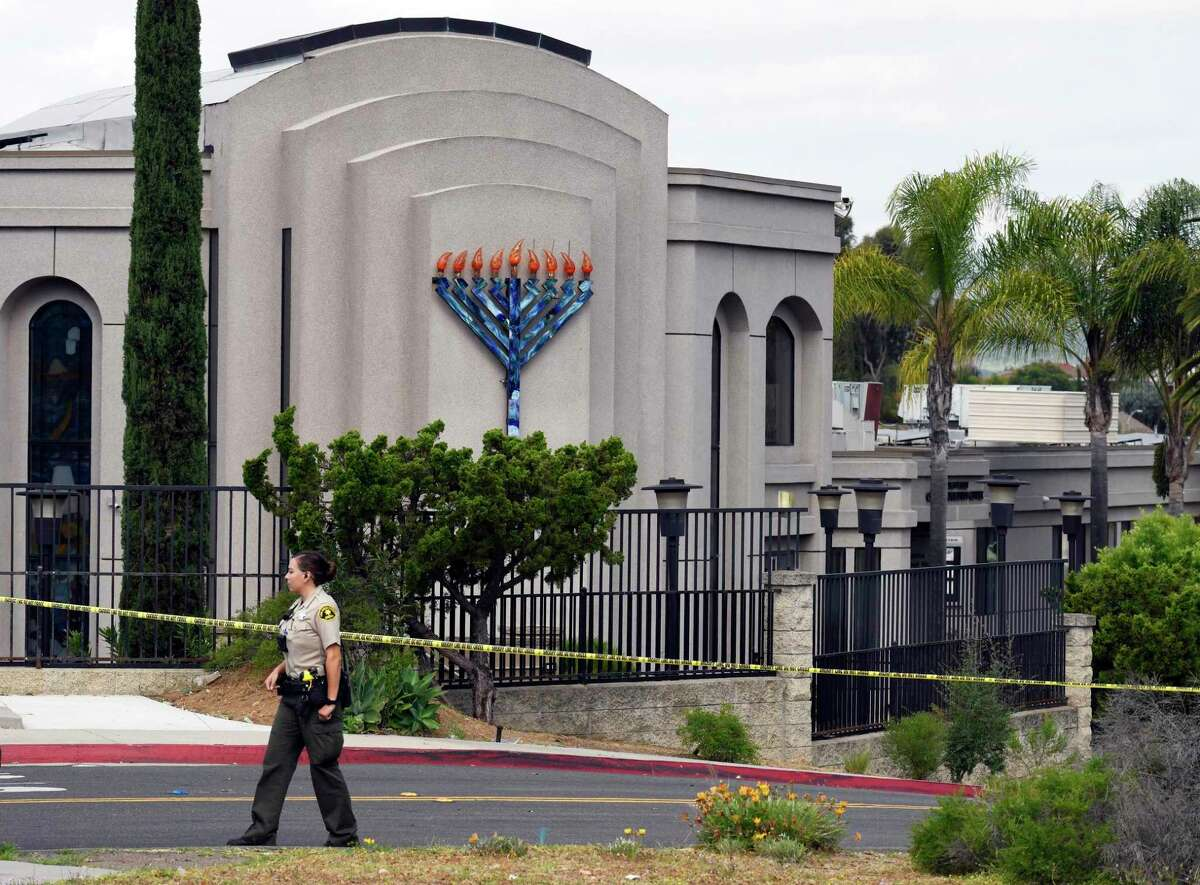 FILE - In this Sunday, April 28, 2019 file photo, A San Diego County sheriff's deputy stands in front of the Poway Chabad Synagogue in April 2019. A gunman who attacked the synagogue killed one person and injured three.
