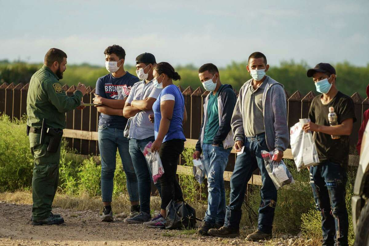 Migrants are processed Thursday in Penitas by U.S. Border Patrol after crossing the border into the United States.