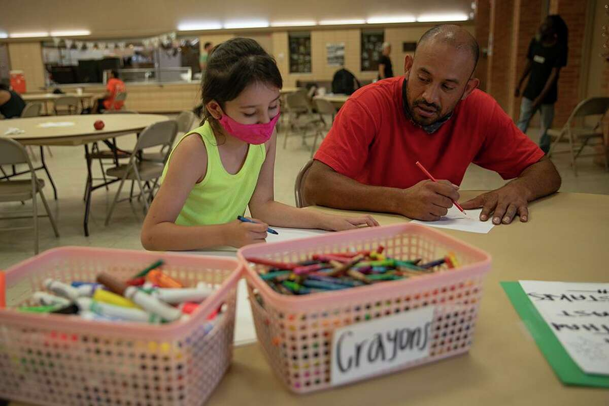 Juan Oliver colors with his niece Domino Esquivel at Corazon Ministries new day center where unhoused people can get in touch with services and escape the summer heat.