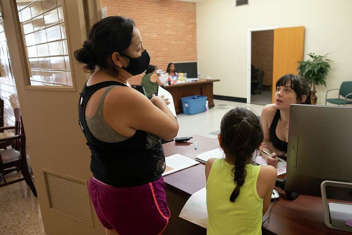 Carmen El Campos talks with a volunteer at Corazon Ministries new day center where unhoused people can get in touch with services and escape the summer heat.