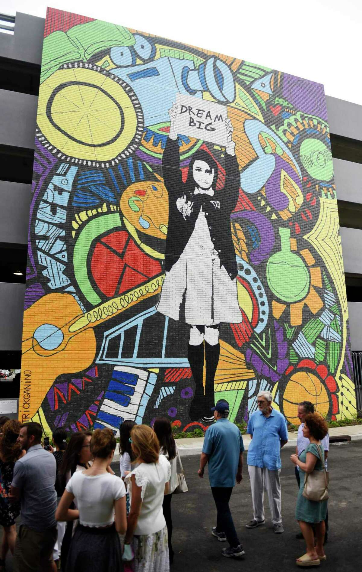 """Folks watch as the """"Dream Big"""" mural is unveiled at The Village in Stamford on Thursday."""