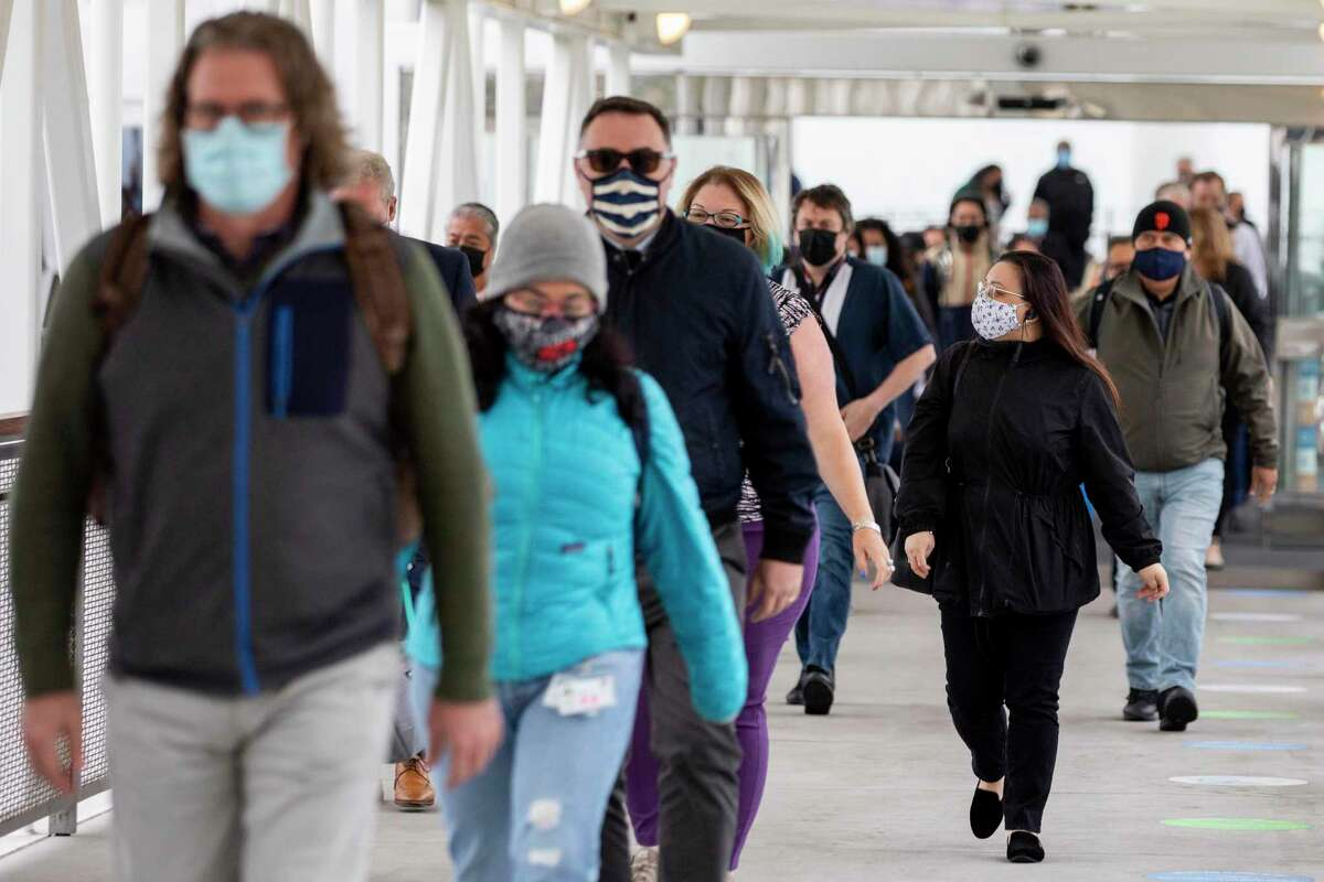 Commuters wear masks while exiting a ferry boat in San Francisco, Calif. Tuesday in early July. While masking has already been required for transportation settings, California has just moved to recommend that everyone wear masks indoors.