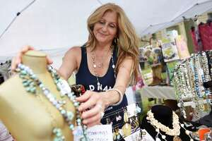 Sophia Scarpelli, owner of Sophia's Gallery, shows jewelry from her popup display at the Greenwich Chamber of Commerce 2021 Sidewalk Sale Days in Greenwich, Conn. Thursday, July 8, 2021. Local businesses displayed items on the sidewalk with extreme savings and markdowns on clothing, jewelry, accessories, gifts and more from participating retailers, restaurants and businesses. The sale continues through Sunday.