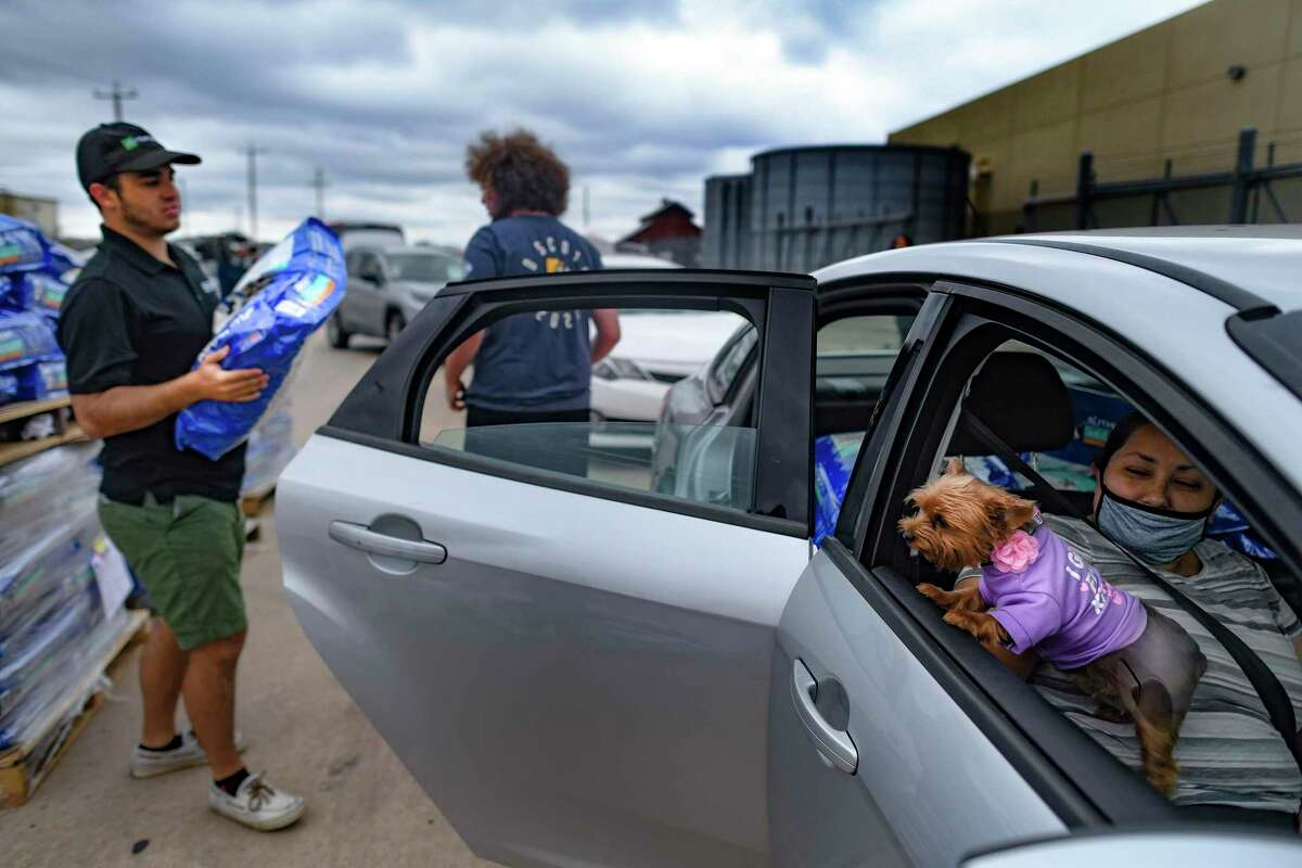 Trudy the dog barks as San Antonio Food Bank volunteers load bags of pet food donated by PetSmart Charities on Thursday, July 8, 2021. With Trudy is Mari Casarez.