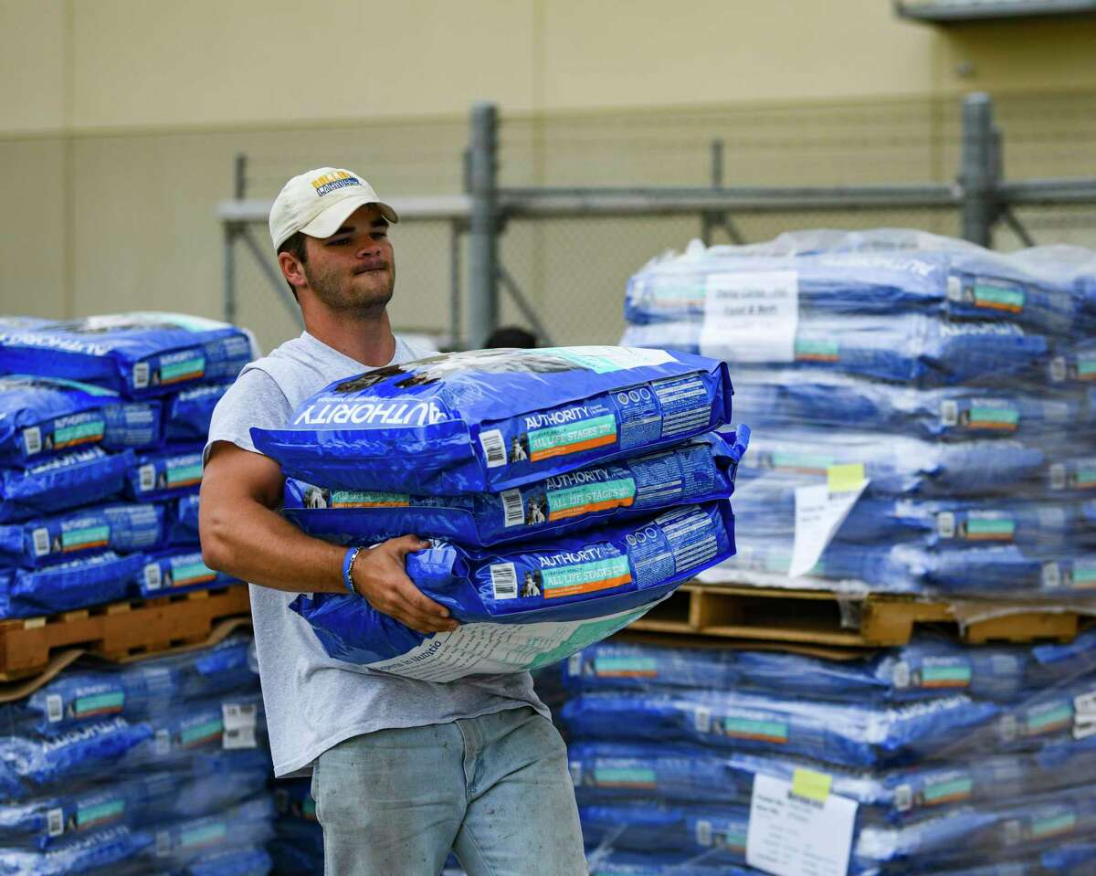 Cameron Reeves, a volunteer from Highland Park United Methodist Church in Dallas, carries some of the 15 truckloads of pet food donated by PetSmart Charities for distribution by the San Antonio Food Bank on Thursday, July 8, 2021.