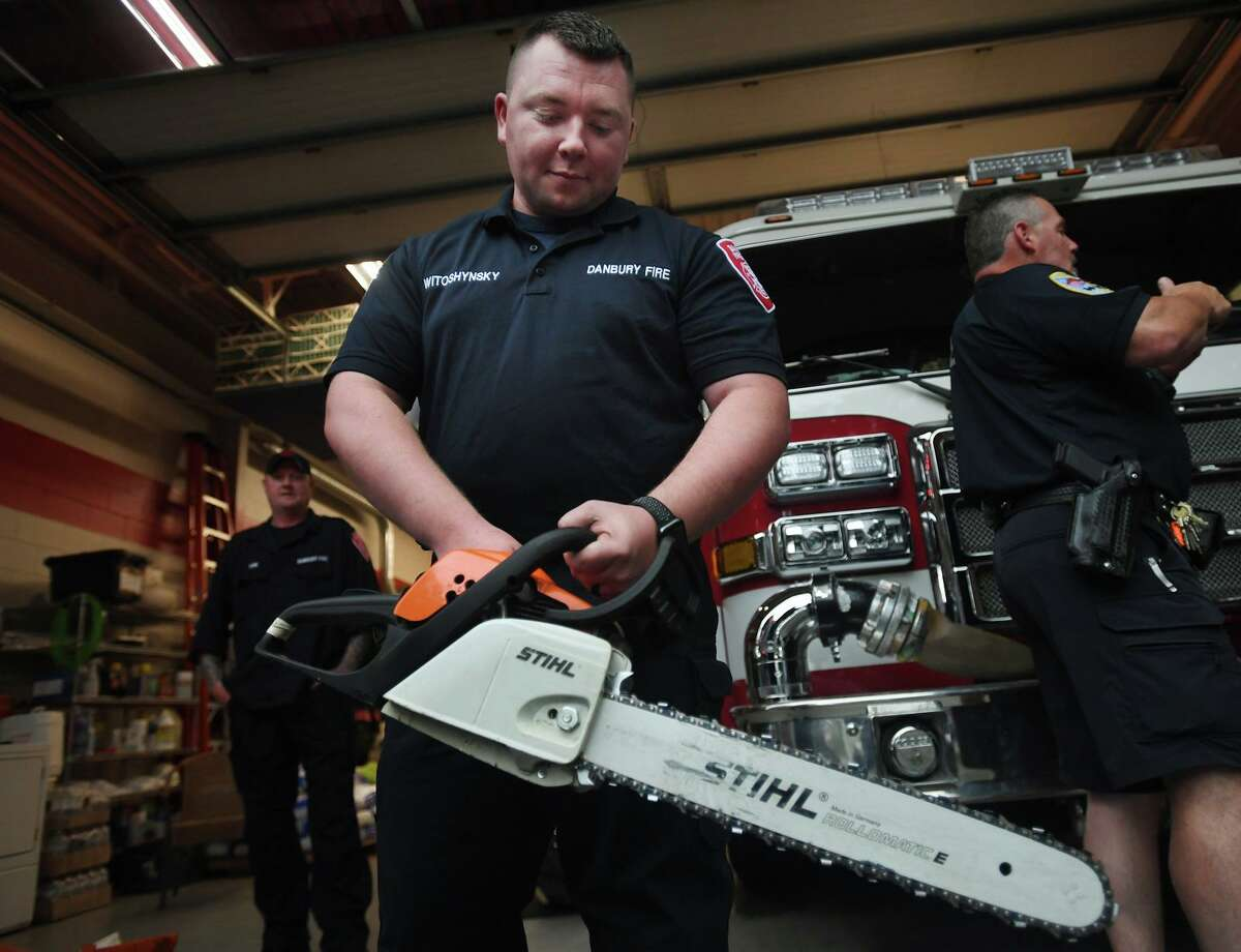 Firefighter Sean Witoshynsky tests his truck's chainsaw Thursday before loading it in preparation for the arrival of storm Elsa in Danbury.