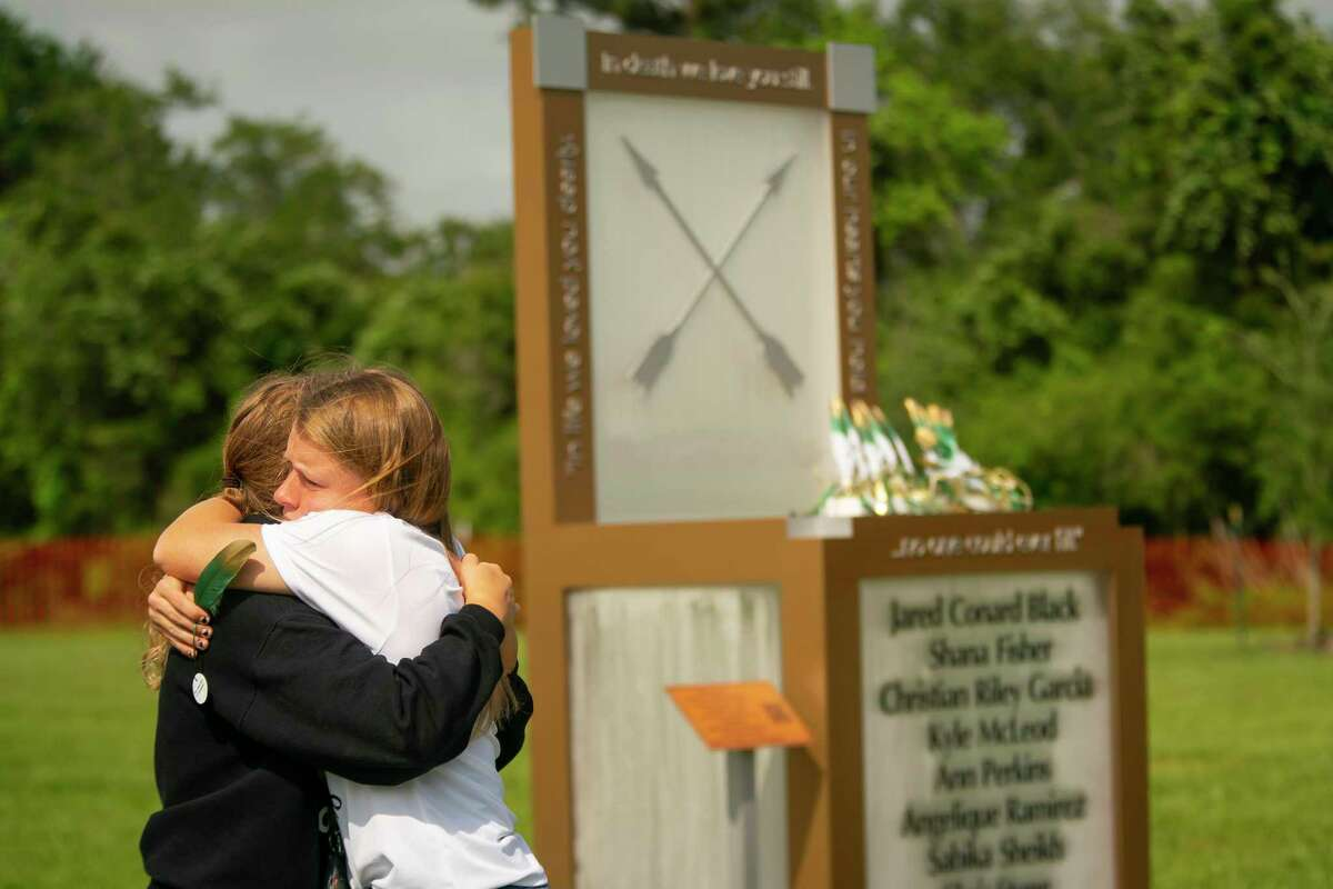 """Chailyn Gillespie, shown shortly before her graduation from Santa Fe High School, hugs a friend next to the new memorial to the 10 victims of the 2018 mass shooting at the high school, following a dedication ceremony, Tuesday, May 18, 2021, outside of the high school in Santa Fe. The Santa Fe Ten Memorial Foundation unveiled the """"Unfillable Chair,"""" a student-designed memorial, on the third anniversary of the shooting. The foundation is planning a larger memorial for the future."""