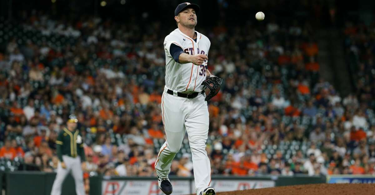 Houston Astros relief pitcher Joe Smith (38) tosses a ball to first base for an out against the Oakland Athletics during the 9th inning of an MLB game at Minute Maid Park on Thursday, July 8, 2021, in Houston.