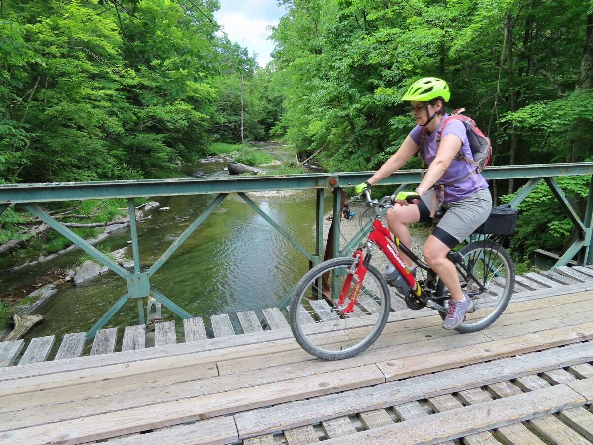 Gillian Scott crosses a bridge over the Poultney River on the Slate Valley Trails.