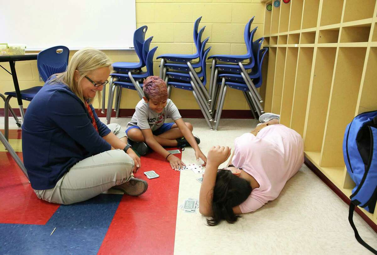 Math teacher Carrie Clewett (left) joins fifth-grade students Cristian Martinez, 11, and Travis Cortez (right), 12, in a multiplication card game Thursday at Coker Elementary School. Area school districts' summer programs are setting records, trying to make up for the learning loss caused by the pandemic and remote learning.