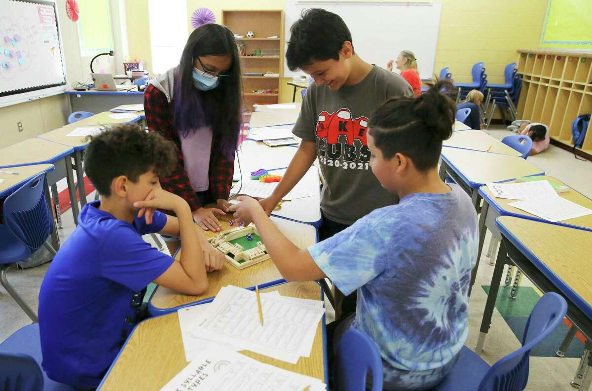Coker Elementary School fifth-grade students Daniel Paez (from left), Judy Aranda, Bruno Gutierrez and Lucius Bonilla play a game that works on their math skills Thursday. Area school districts' summer programs are setting records, trying to make up for the learning loss caused by the pandemic and remote learning.