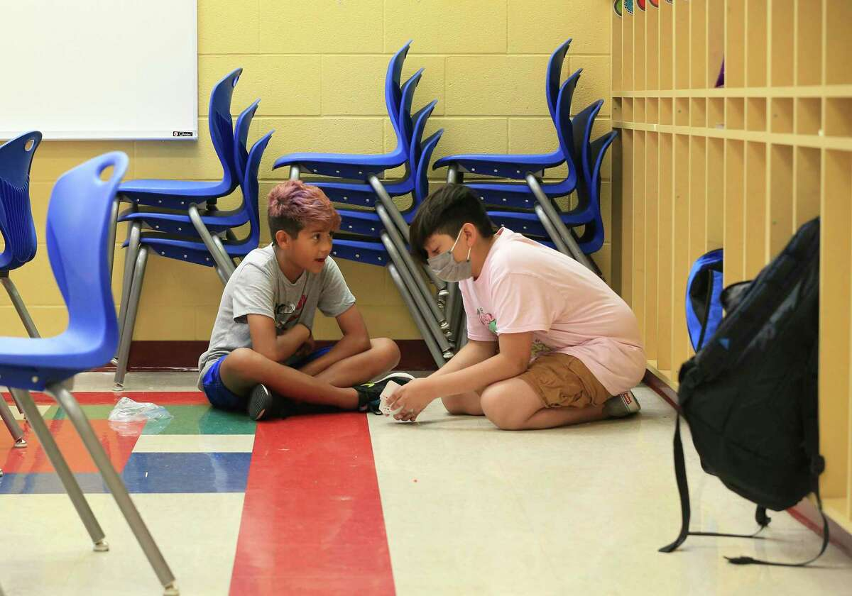 Coker Elementary School fifth-grade students Travis Cortez (right) and Cristian Martinez play a multiplication card game Thursday. Area school districts' summer programs are setting records, trying to make up for the learning loss caused by the pandemic and remote learning.