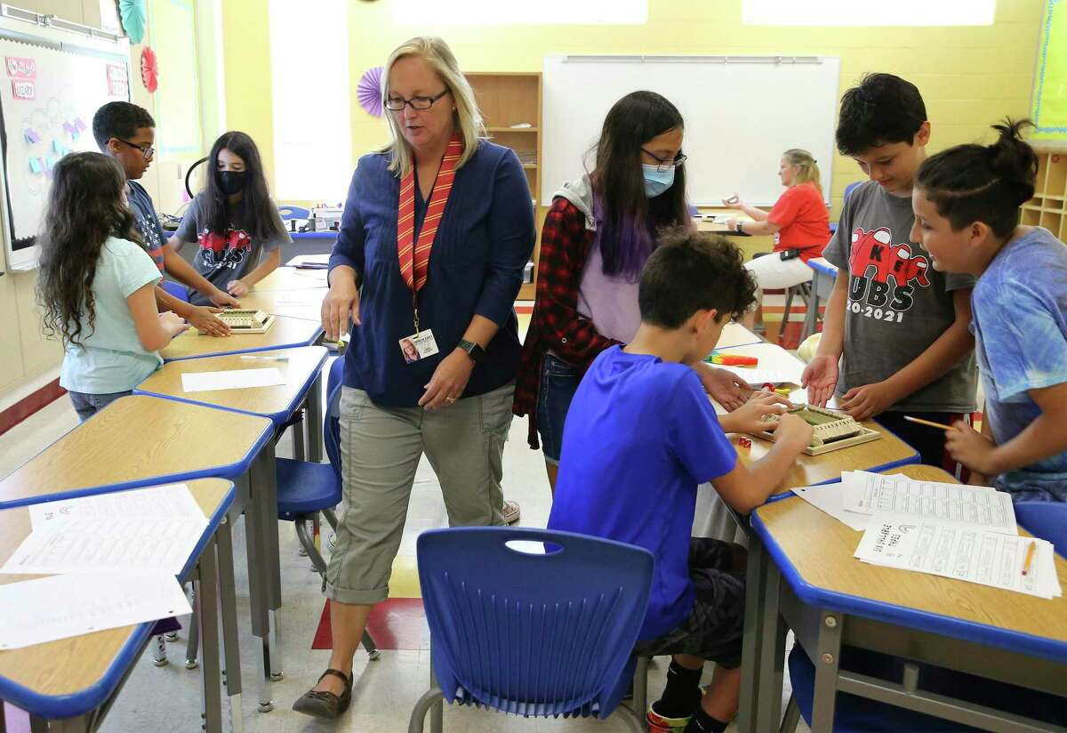 A teacher walks through a classroom at Coker Elementary School earlier this month. Masks are optional, younger children can't get vaccinated and the delta variant is surging.