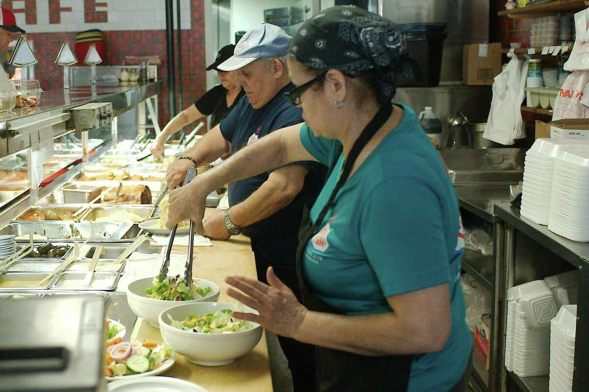 Teresa Meza, Pete Bogdanos and Maria Godiness serve customers at the steam table during the lunch rush.