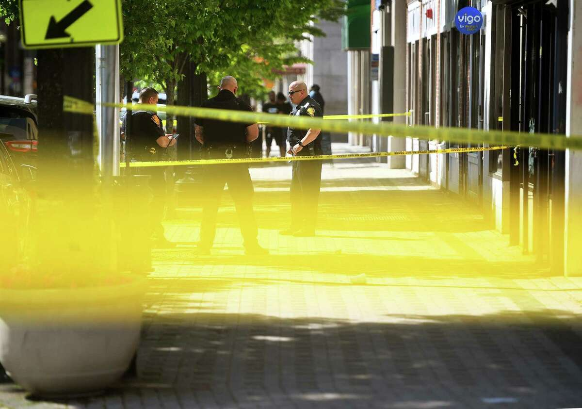Yellow police tape marks off the crime scene as Bridgeport police investigate a double homicide in the heart of the city's downtown May 16, 2021.
