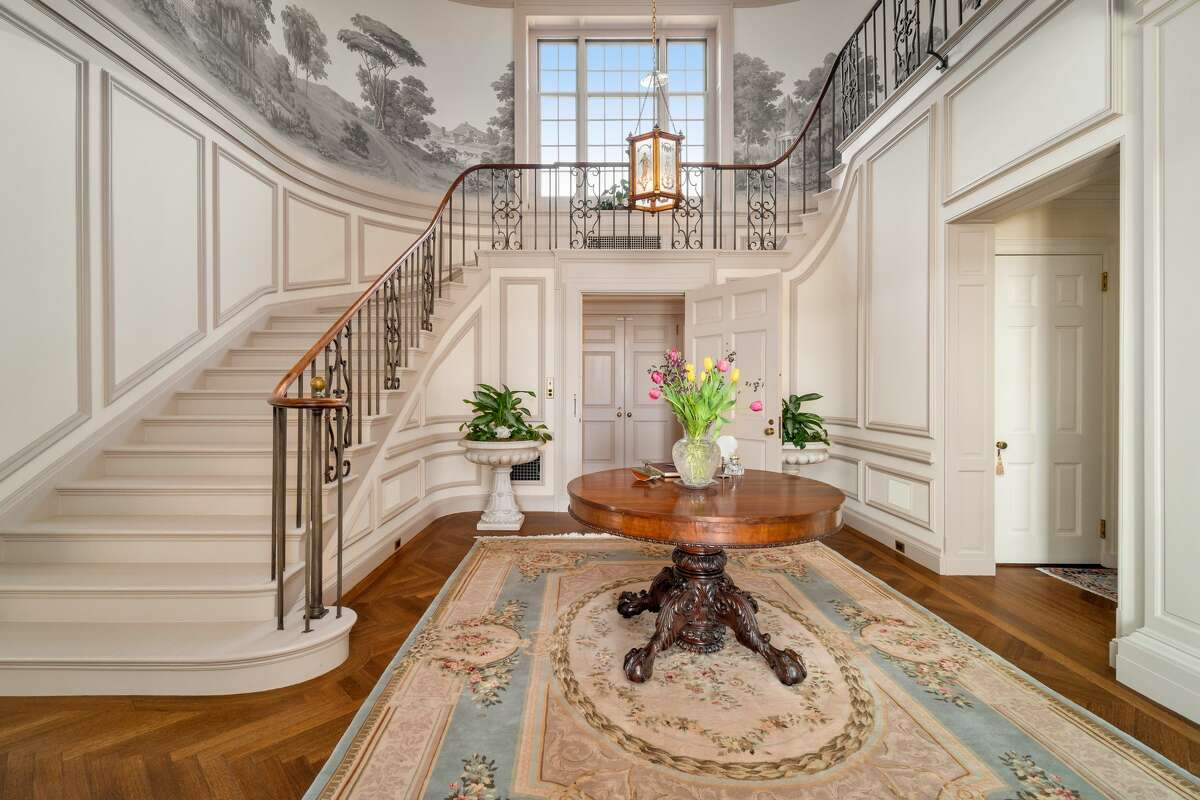 The entry hall in the Cheneymansion features a grand staircase and high ceilings.
