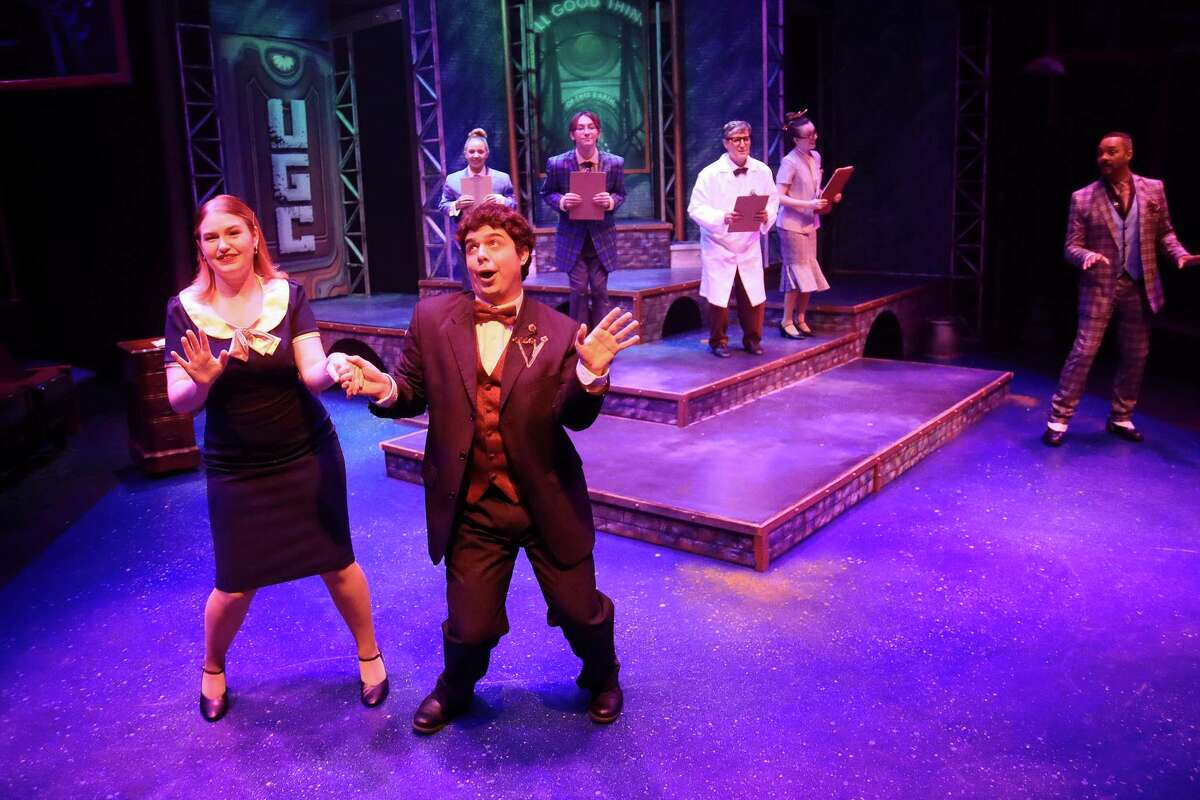 """Hope Cladwell (Zoe Temple) and Mr. McQueen (Jase O'Brien) help the employees of UGC sing the praises of their power-mad boss in """"Urinetown."""""""