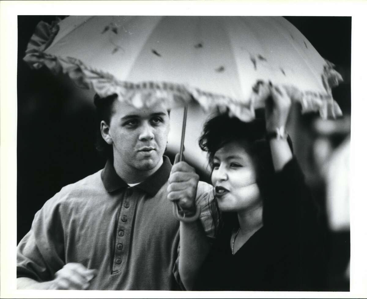 Rob Long and Debbie Valdez try to keep dry on a Sunday afternoon during Cinco de Mayo celebrations held at Market Square, 1994.