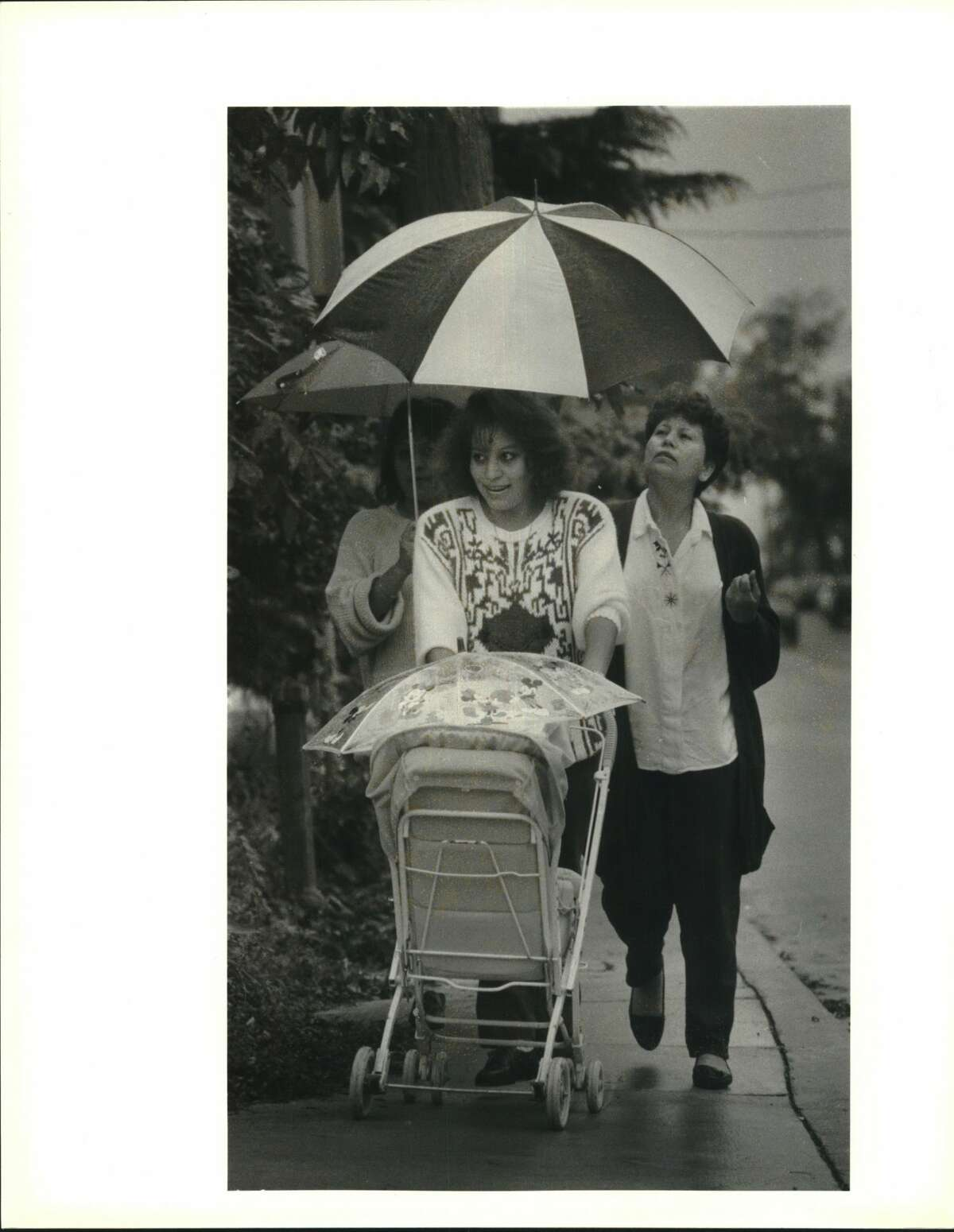 Caught on the corner of West Ashby and Main in 1993. Norma Aldape pushes her 11-month-old daughter Janessa Aldape in a stroller while Antonia Aldape tries to keep both of them dry during the rain.