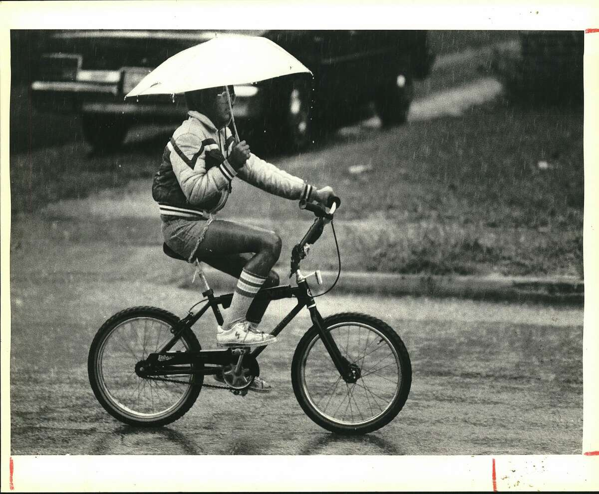 Danny Garza rides a bike on a rainy day down East French Street.