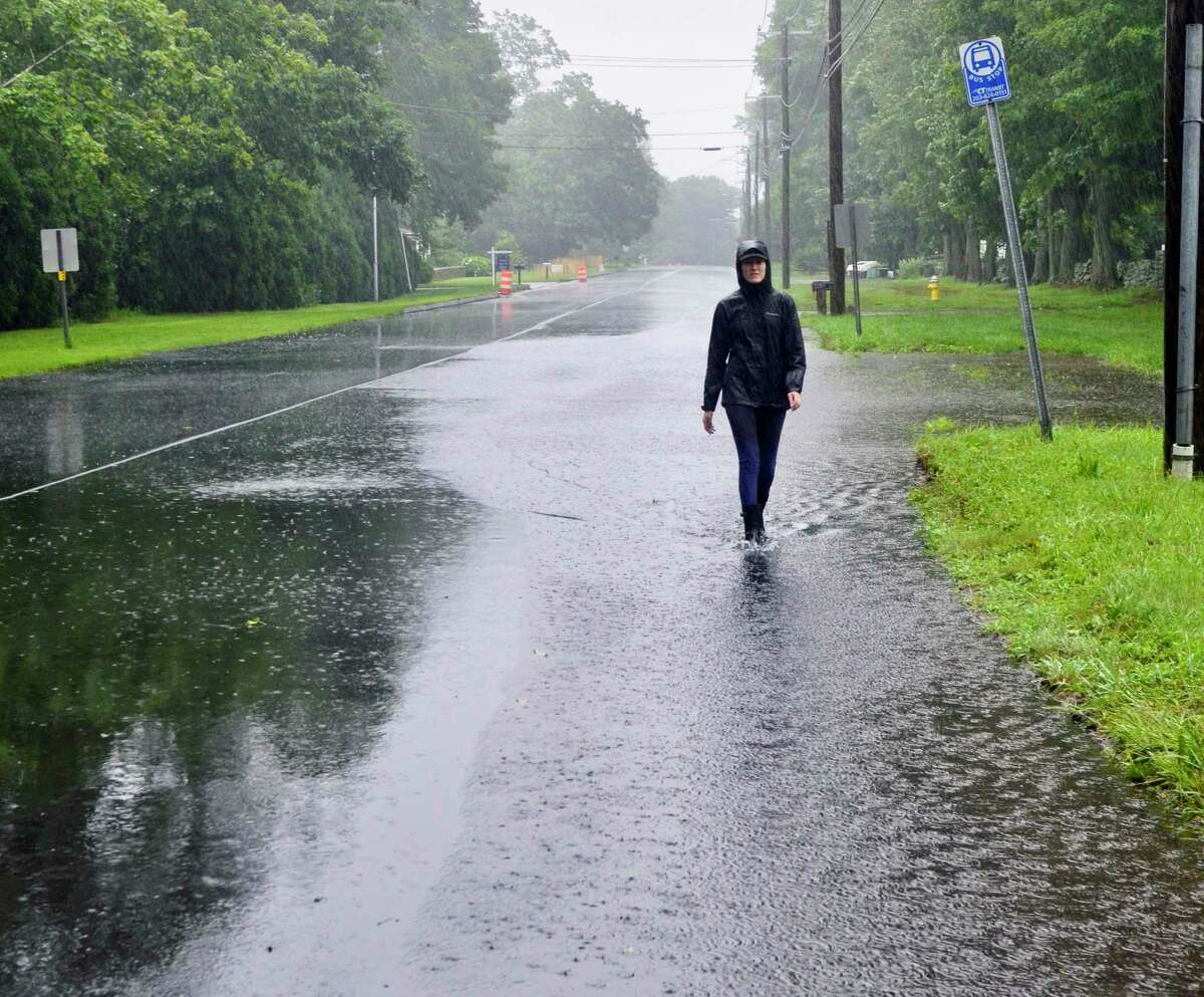 An individual walks along Route 1 in Madison Friday morning as streets began to flood from Tropical Storm Elsa's heavy rain.