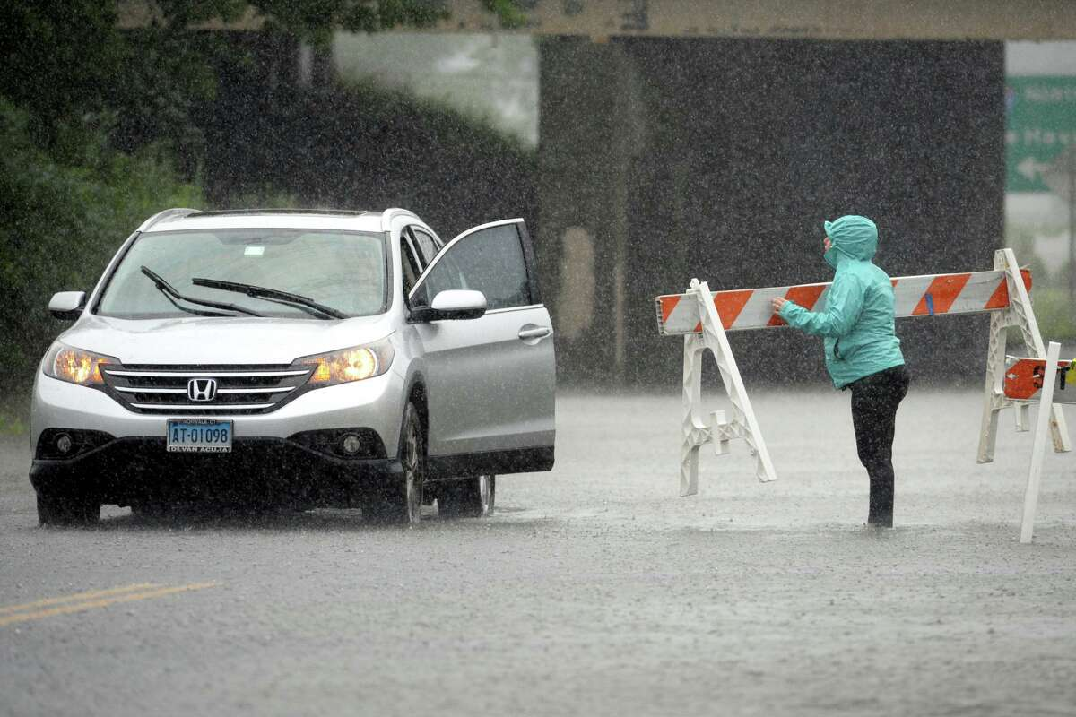 A woman works to get her car through a flooded section of Surf Ave., in Stratford, Conn. July 9, 2021.