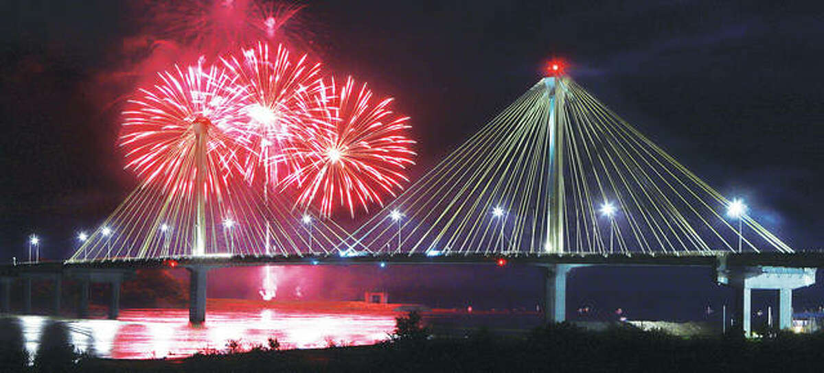 Fireworks explode behind the Clark Bridge in Alton Saturday night. Thousands came out to watch downtown and along the top of the levee in Alton.