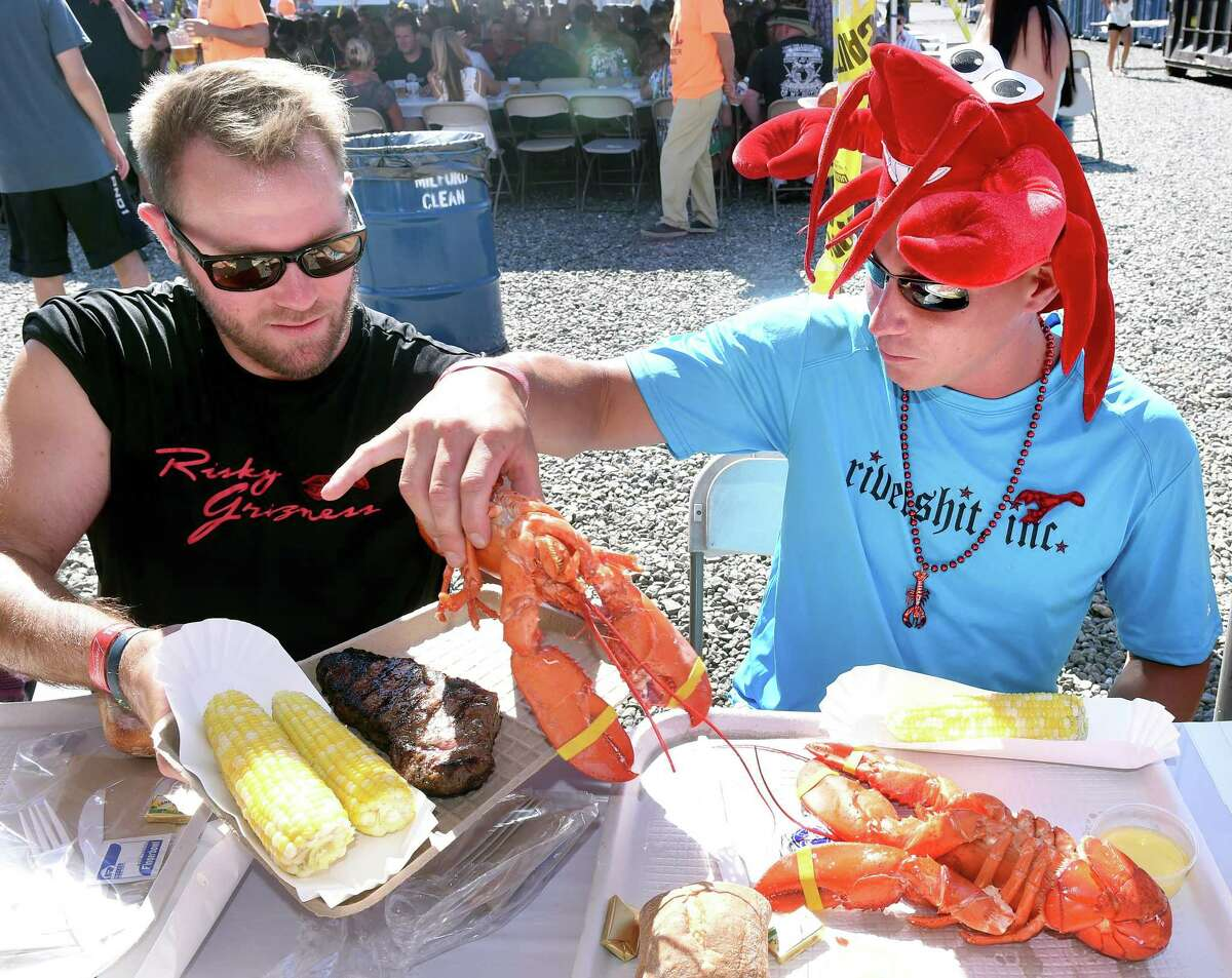 Travis Bokina (left) trades half of a steak for a lobster with Daniel Krotki at the Milford Rotary's 40th Annual Lobster Bake at Milford Boat Works on 7/23/2016. Both are from Milford. The 2021 fundraiser has been canceled, marking the second year COVID-19 has impacted the annual event.
