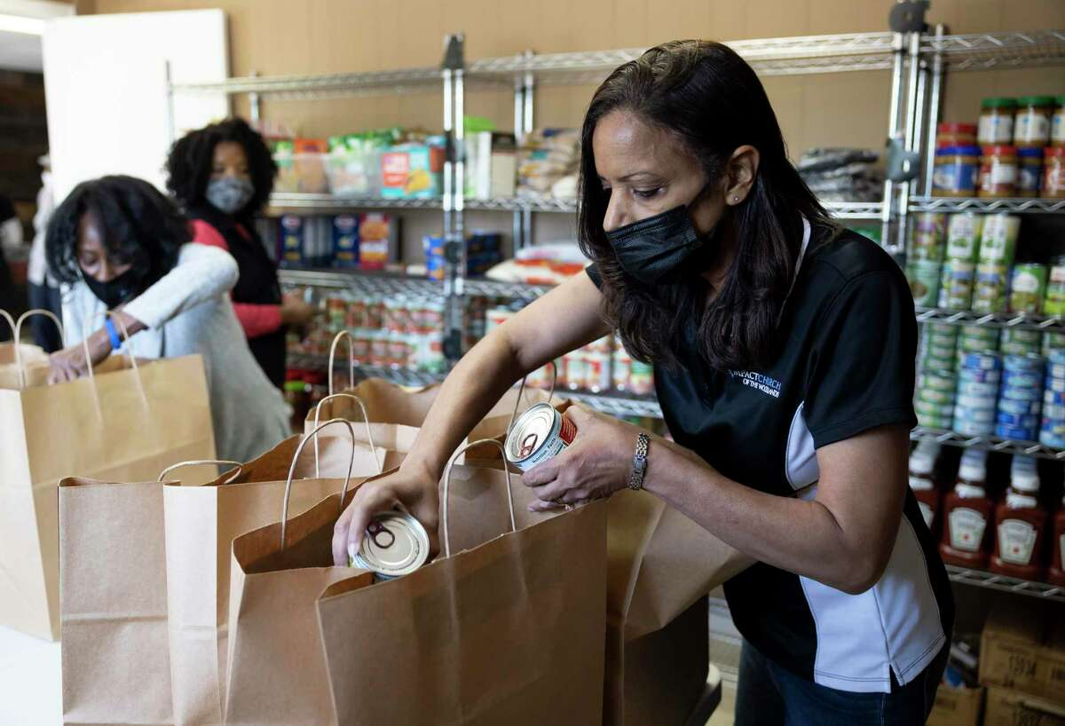 JoBess Shaw, right, loads food items into bags at Impact Church's food pantry, Wednesday, April 21, 2021, in The Woodlands. The food pantry was opened in March to assist families and individuals facing food insecurity.