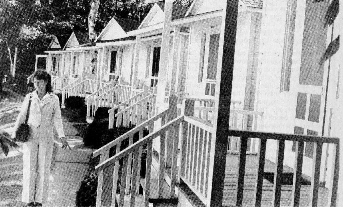 """Pat Hare, of West Shore Realty, examines six """"dollhouses"""" at Onekama's Portage Point In which is being converted from a rental resort to purchase-type condominium units. A total of 25 units are being put up for sale in a move which promoters hope will save the """"old time family hotel"""" atmosphere of the 79-year-old resort. The photo was published in the News Advocate on July 10, 1981. (Manistee County Historical Museum photo)"""