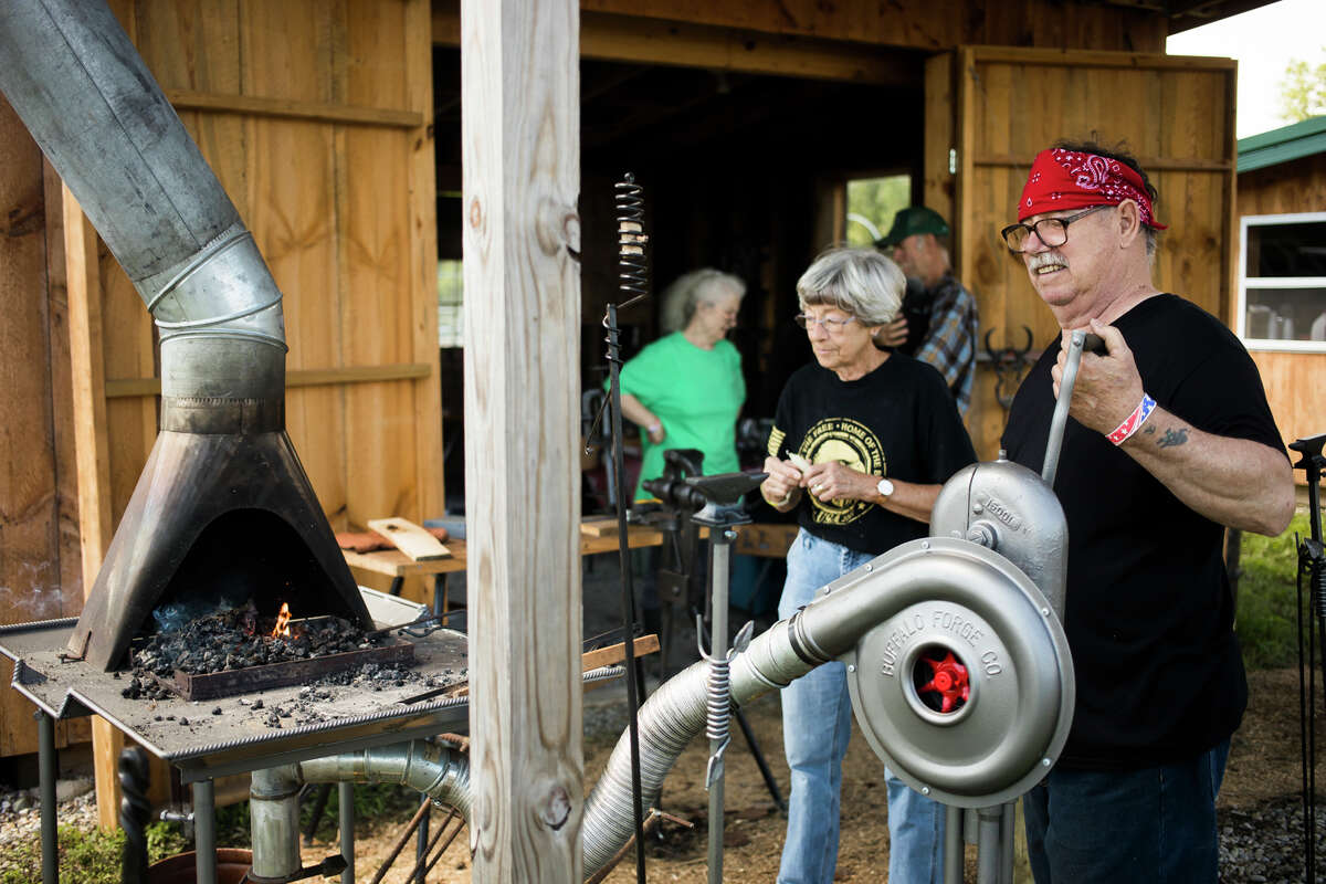 Blacksmith Donald Robinson of Sanford, right, creates a candle holder for Gloria Eldred of Shepherd, center, as engine enthusiasts gather for the first day of the 33rd Annual Midland Antique Engine Association Tractor Show Friday, July 9, 2021 at 3226 S. Meridian Rd. in Merrill. (Katy Kildee/kkildee@mdn.net)