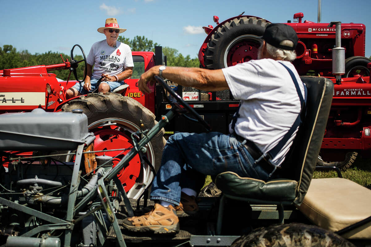 Roy Shankel of Breckenridge, left, chats with Dwayne Dysinger of Clare, right, during the first day of the 33rd Annual Midland Antique Engine Association Tractor Show Friday, July 9, 2021 at 3226 S. Meridian Rd. in Merrill. (Katy Kildee/kkildee@mdn.net)