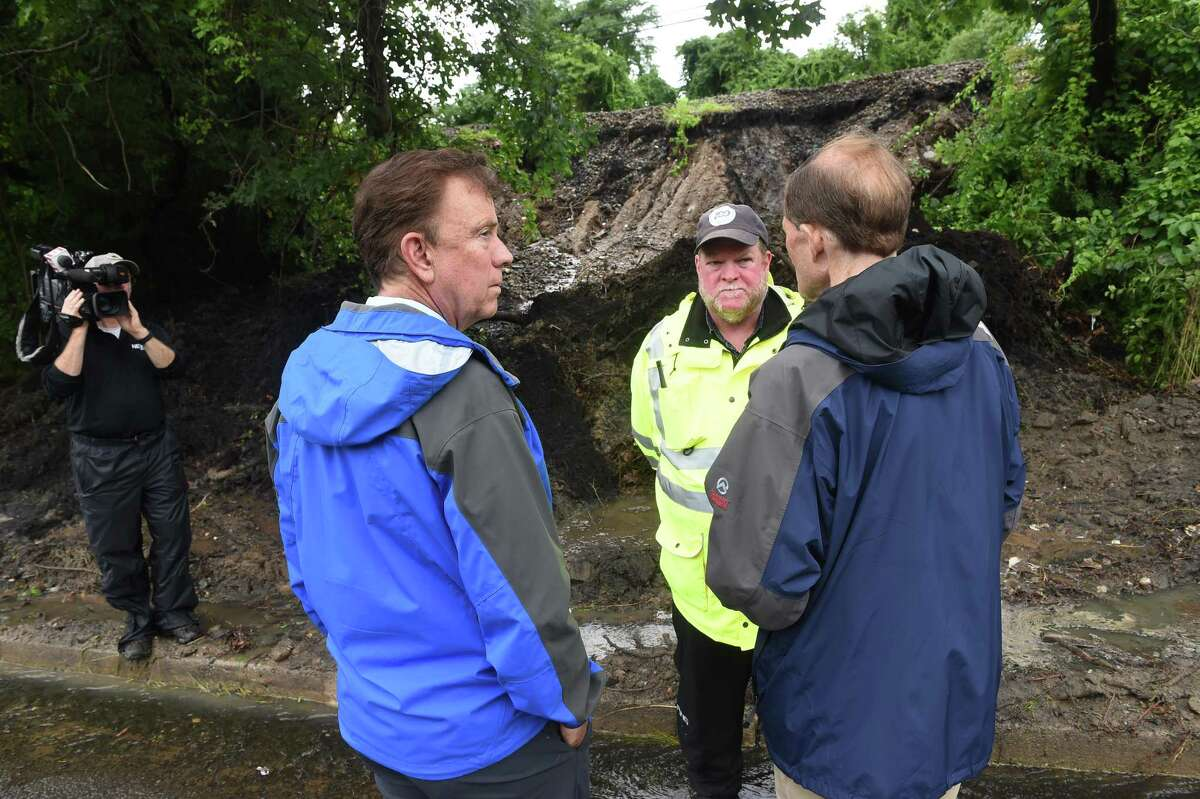 Governor Ned Lamont (left) and Senator Richard Blumenthal (right) speak with West Haven Commissioner of Public Works, Tom McCarthy (center), at an area where a mudslide occurred next to train tracks along Callegari Drive in West Haven following heavy rain from Tropical Storm Elsa on July 9, 2021.
