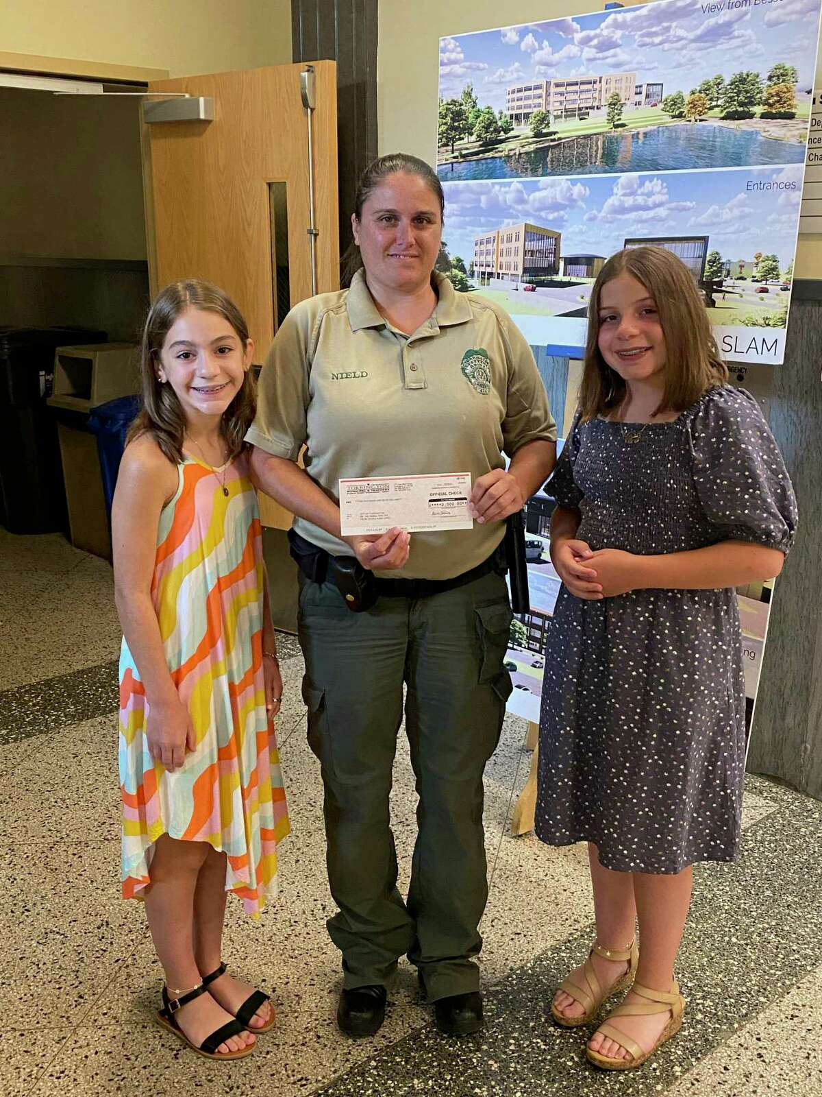 Julia Lopez, 11, right, and her sister Alina, 13, made a donation of $2,000 to the city's animal shelter project July 7 during the Board of Public Safety meeting. With them is Animal Control Officer Caitlin Nield.