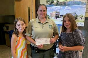 Julia Lopez, 11, right, and her sister Anna, 13, made a donation of $2,000 to the city's animal shelter project July 7 during the Board of Public Safety meeting. With them is Animal Control Officer Caitlin Nield.