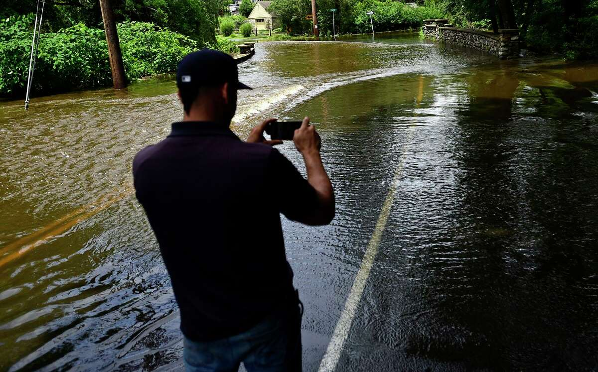 An employee for Yale Pets Control photographs flooding that closed Greens Farms Road at Center Street in Westport on Friday.