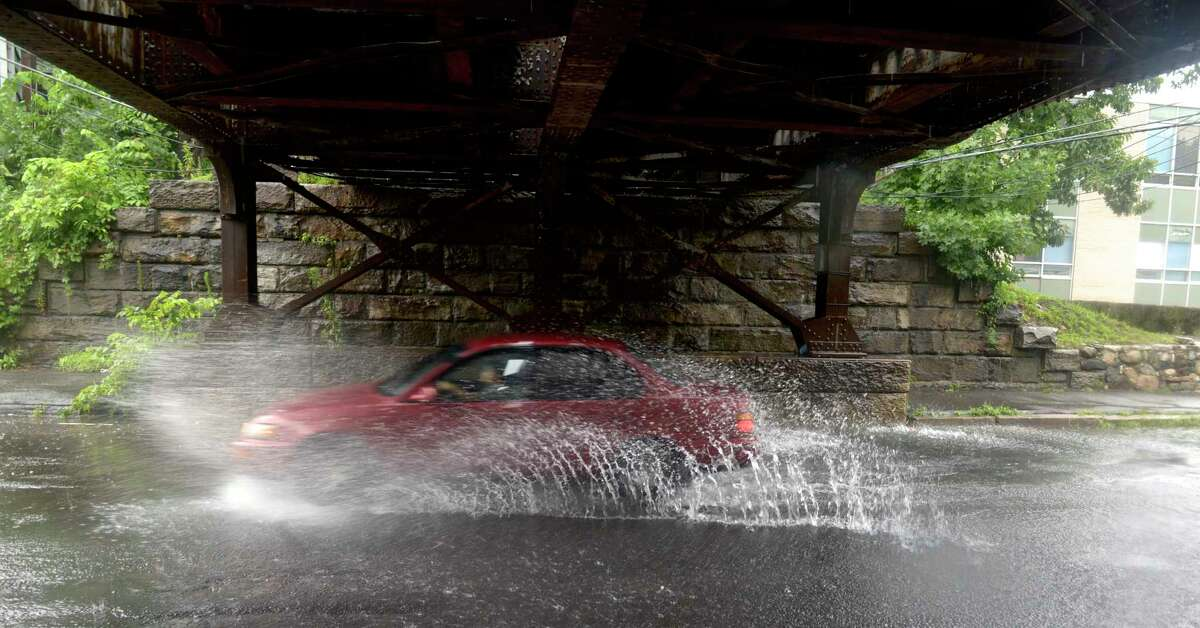 A car splashes through a puddle under the rail bridge over West Street on Friday. Water from heavy rains caused some road flooding in Danbury, Ct, on Friday, July 9, 2021.
