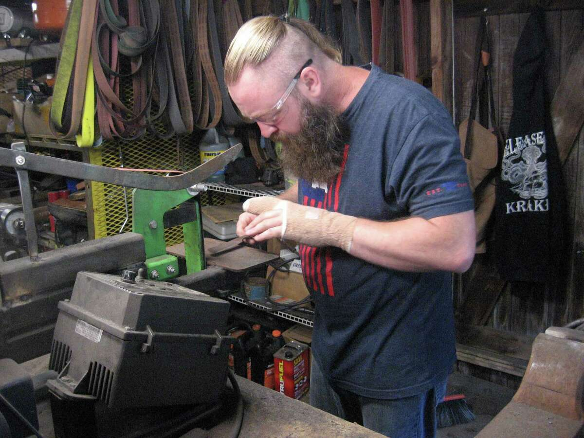 Jerrod Sutcliffe works in his forge in Torrington. Sutcliffe, a Navy veteran, says his work helps with the mental and physical effects of his time fighting in Iraq.