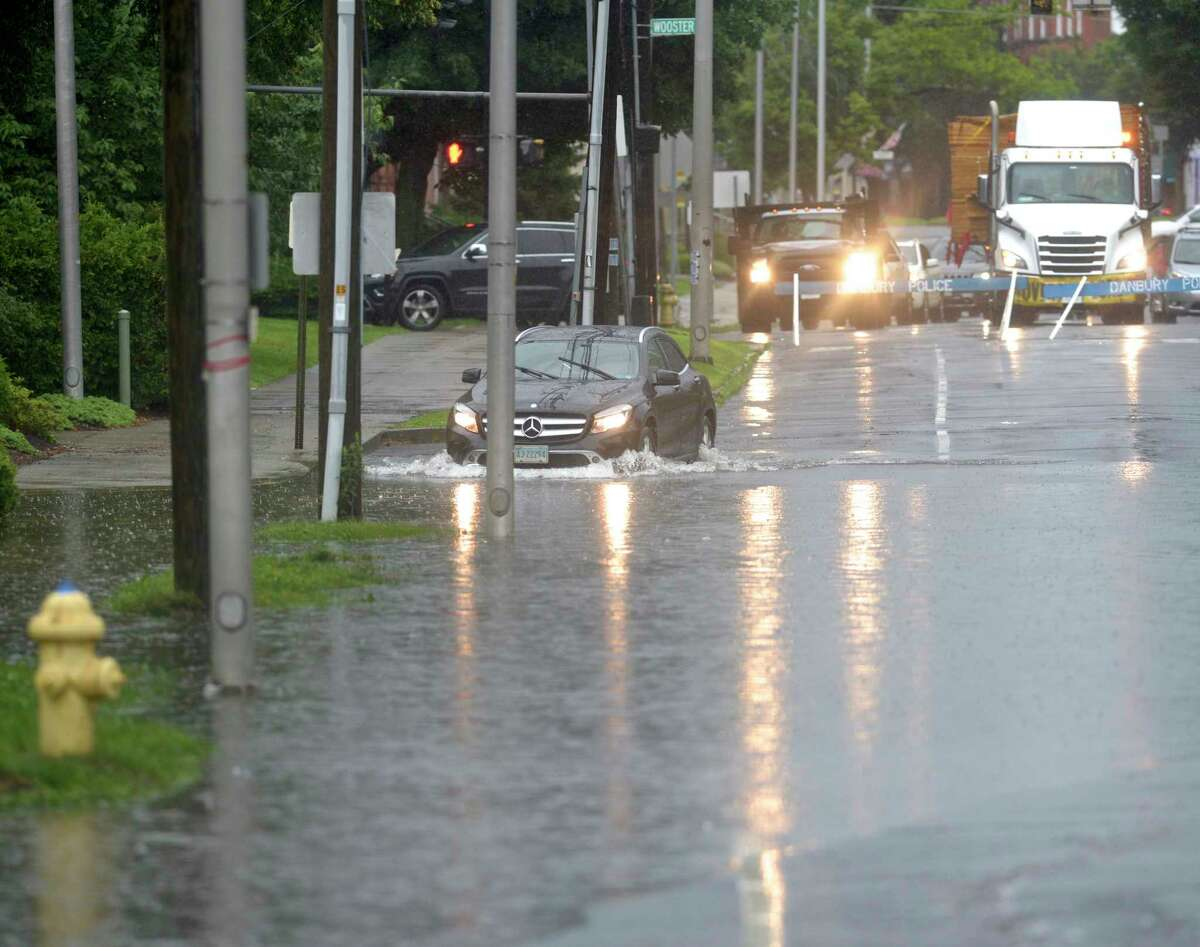 An SUV enters the water flooding a section of Main Street by Main Street Park. The road was blocked off at Wooster Street because of flooding from tropical storm Elsa, in Danbury, Ct, on Friday, July 9, 2021.
