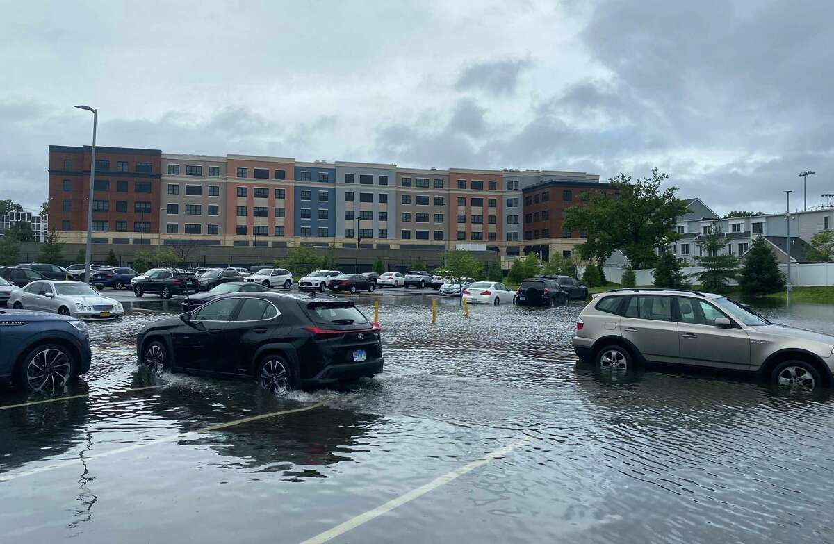 A car slowly drives out of a flooded surface lot at Stamford Health in Stamford on Friday.