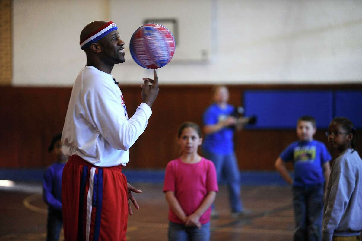 """The Harlem Globetrotter's Aundre """"Hot Shot"""" Branch spins a ball during a show for Hamshire Fannett Elementary students."""