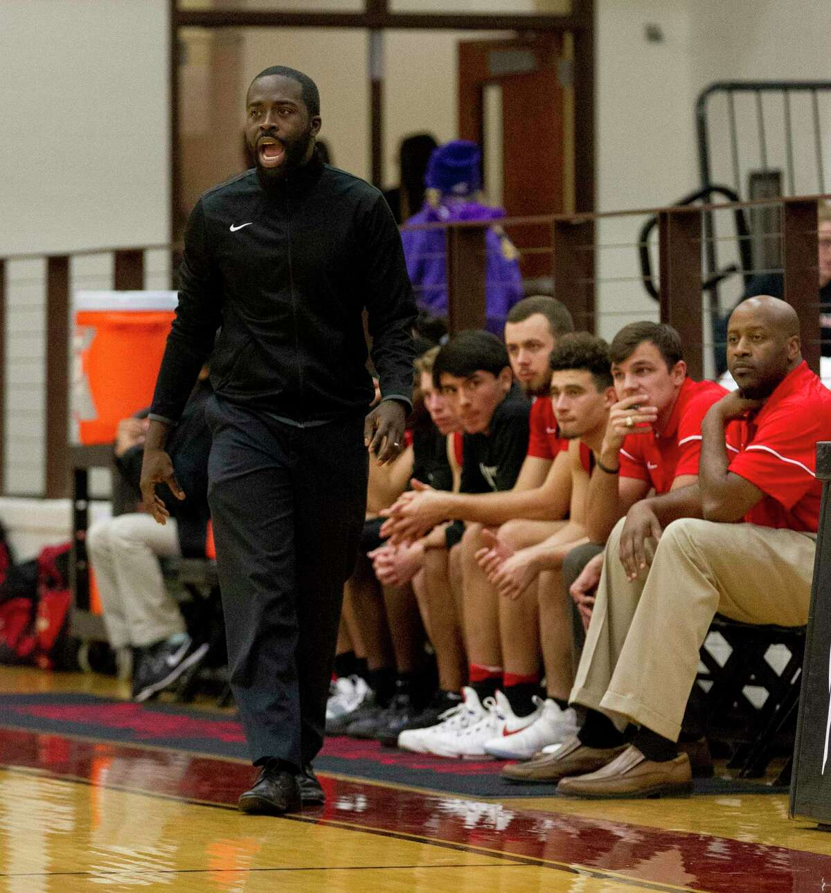 Caney Creek head coach Randy Appiah shouts instructions to players during a 2017 game at Porter. Aundre Branch is first from the right on the bench.