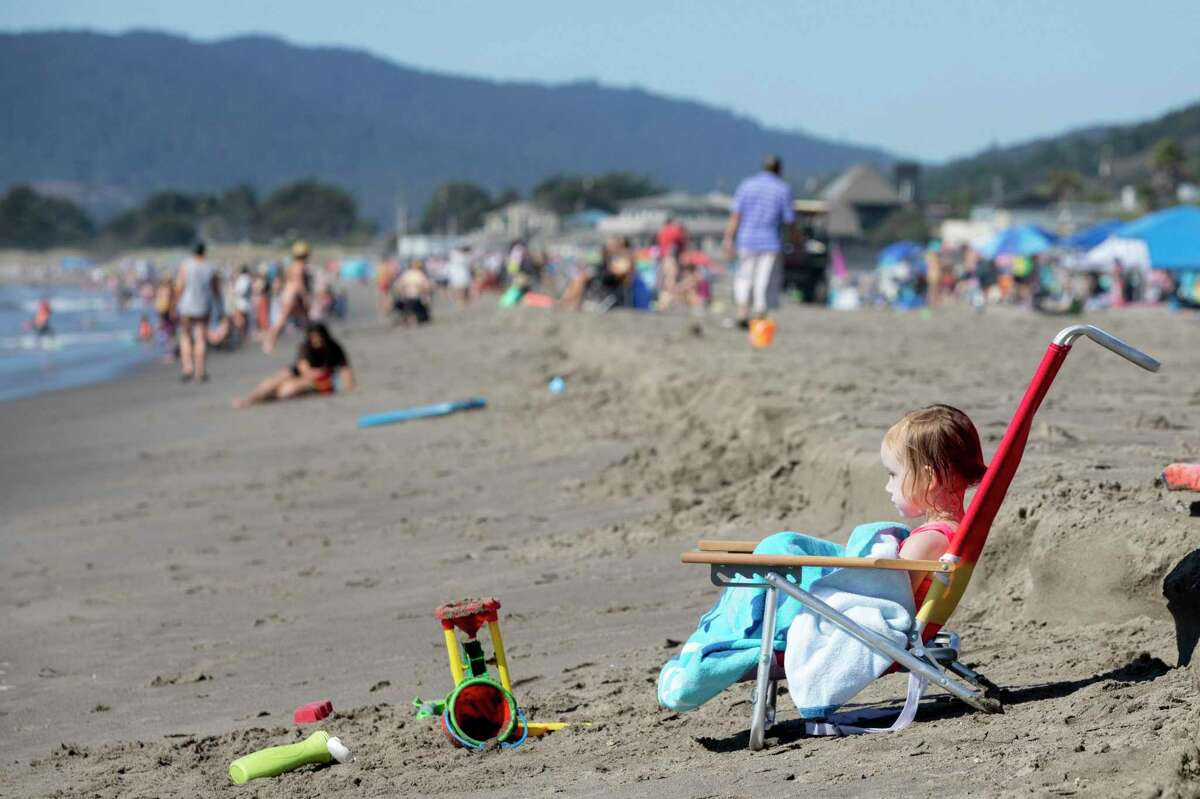 A young girl sits on her own beach chair while looking at the waves as crowds gather to enjoy the warm weather at Stinson Beach in Stinson Beach, Calif. Another heat wave descending on much of California was expected to push temperatures above 100 in some parts of the Bay Area and prompted an excessive heat warning that will last through late Sunday.