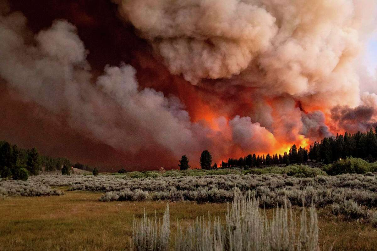 Plumes of smoke and fire rise above Frenchman Lake as the Sugar Fire, part of the Beckwourth Complex Fire, burns in the Plumas National Forest.