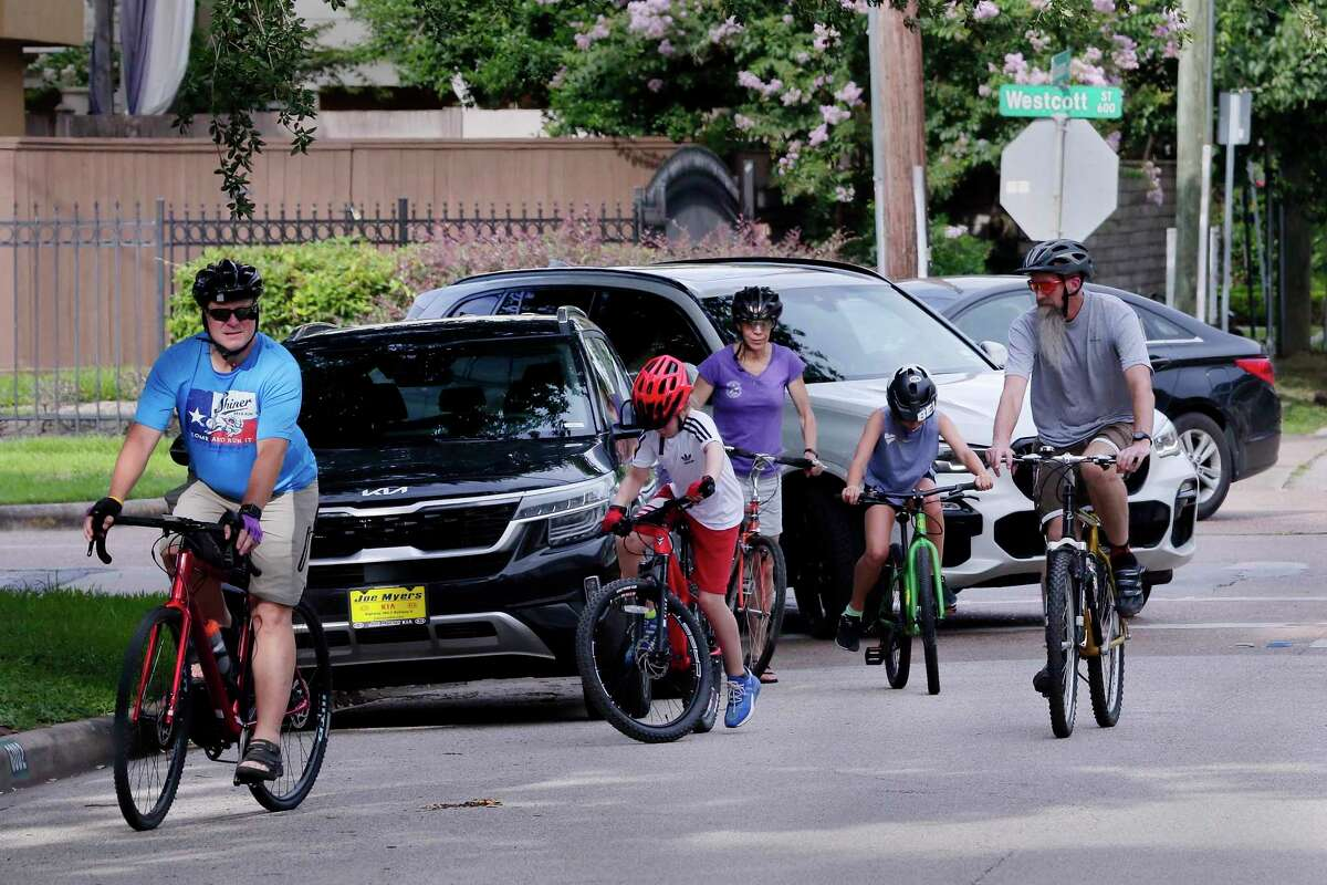 Adults and children on bikes negotiate breaks in traffic as they cross Westcott on Blossom near Memorial Park on July 7, 2021. Memorial Park is seeing improvements, but the access areas around the park for those who use it have not seen many improvements.