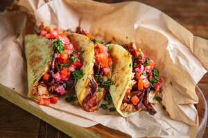 Serving of tacos with shredded roast pork and cheese filling, garnished with caramelized spanish onion and chopped tomato salsa sauce