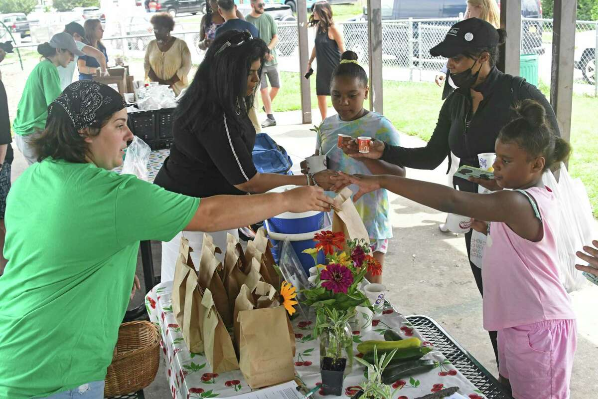 Leah Egnaczyk hands over a bag of popcorn to Naliyah Boothman as Schenectady Inner City Ministry holds a Free Summer Meals Kick-Off Event at Jerry Burrell Park on Friday, July 9, 2021 in Schenectady, N.Y. The program said Aug. 16, 2021 that it had to reduce the number of meals provided because of staffing shortages and a COVID-19 case that caused quarantines. (Lori Van Buren/Times Union)