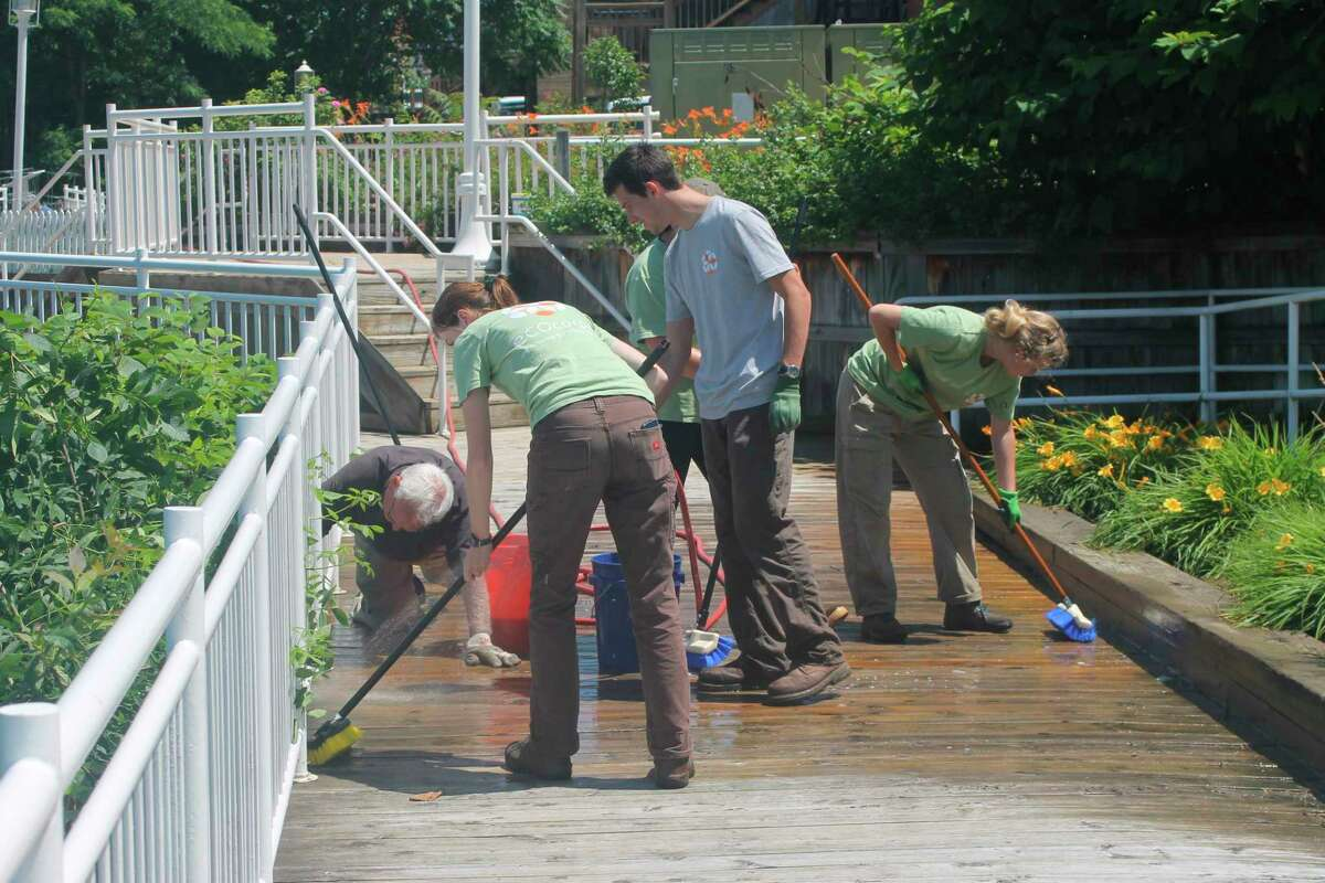 Members of Manistee SEEDS clean the Riverwalk Friday to help Manistee Proud accomplish its goal of restoring it to its former glory. (Kyle Kotecki/News Advocate)