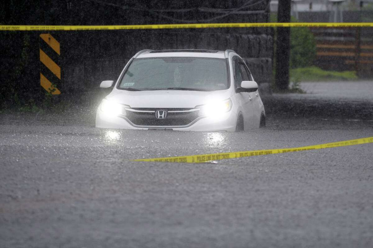 A car sits stranded in flood waters from tropical storm Elsa on East Main St., in Stratford, Conn. July 9, 2021.