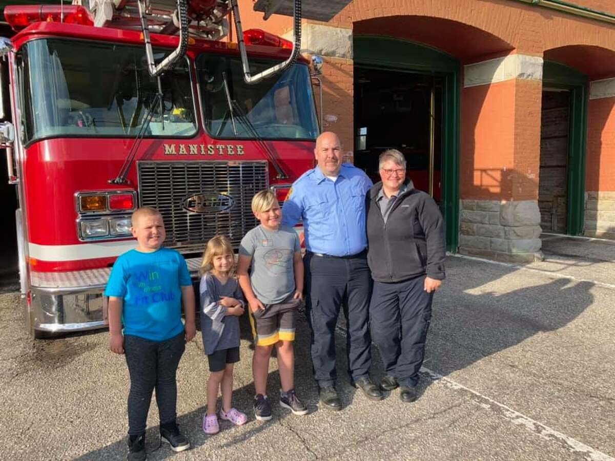 Matt Witkowski (center right) is shown with his family after a pinning ceremony at the Manistee Fire Department in June.